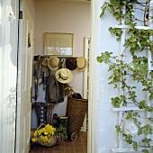Garderobe mit Hüten und Jacken, zu sehen durch eine offene Haustür, daneben eine Kletterpflanze mit Spalier