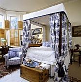 Schlafzimmer mit Himmelbett, blau-weiss gemusterten Bett-Vorhängen und mit Bambus-Innen-Fensterläden