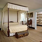 Schlafzimmer im kolonialen Stil mit cremefarbener Bettdecke auf dem Himmelbett, kleiner antiken Holztruhe und Holzboden