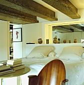 Ein Doppelbett mit weisser Bettwäsche in einem Schlafzimmer mit großen hölzernen Deckenbalken