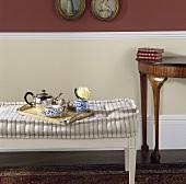 Tablett mit Teekanne und Tassen auf einem Hocker mit gestreiftem Sitzkissen