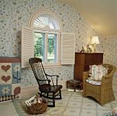 Schaukelstuhl aus Eichenholz und Korbsessel im Schlafzimmer mit floralen Tapeten und weissen Fensterläden vor einem Bogenfenster