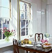 Marmortisch, für das Frühstück gedeckt, vor den Fenstern mit weissen Fensterläden