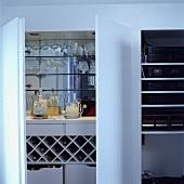 Barutensilien, Gläser und Weinregal in einem Schrank mit weissen Türen