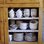Porzellantassen und Teller auf Regalen in einem Holzschrank