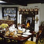 Gedeckter Frühstückstisch vor einem Kamin mit brennendem Feuer in einem ländlichen Esszimmer