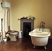 Frei stehende Badewanne mit Holzablage und Toilette in einem Badezimmer mit Holzboden und kleinem Kamin