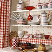 Rot-weisses Geschirr in einem Küchenregal mit rot-weiss karierten Gardinen