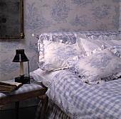 Tapete und Kissen mit dem gleichen Toile-de-Jouy-Muster und blau-weiss karierte Bettdecke in einem Schlafzimmer