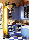 Küchenecke mit blauen Einbauschränken im Landhausstil und Schachbrettmusterboden