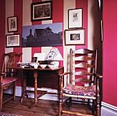 Antiker Stuhl und Tisch vor moderner rot weiß gestreifter Wohnzimmerwand