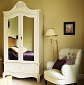 Antik weiss lackierter Schrank mit Spiegeleinsätzen in Tür neben Polstersessel im hellgelb getönten Schlafzimmer