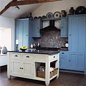 weiße freistehende Küchentheke vor Küchenschrank und -zeile mit blau getönten Fronten im Landhausstil