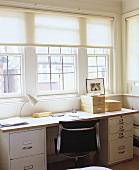 Home office mit Tischplatte aus Holz über Container und Schreibtischstuhl aus schwarzem Leder und Chrom vor Fensterfront