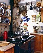 Vintage Küchenecke mit schwarz lackiertem Herd und gemusterten Tellern im Wandboard