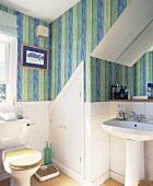 Kleines Bad unter Dachschräge mit StandWC und – Waschbecken vor halbhoher weiss gefliester Wand und gestreifter Tapete