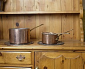 Kupferpfannen auf antiker Holzkommode