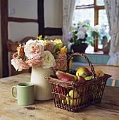 Korb mit Birnen und Rosenstrauss im Krug neben grüner Tasse auf Holztisch
