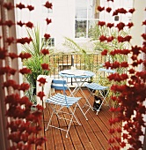 Blick durch Glastür auf Balkon mit blauen Gartenstühlen auf Holzterrasse