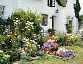 Blühender Garten vor weiss getünchter Fassade eines Landhauses