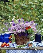 Wiesenblumen im Korb neben blauen Kannen auf dem Tisch