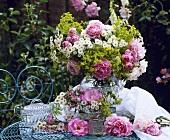 Rosa Rosen und Wiesenblumen in Glasvase auf Gartentisch