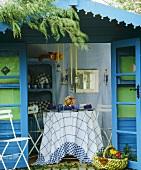 Blau gestrichenes Gartenhaus mit offenen Türen und und Blick auf gedeckten Tisch