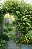 Geziegelter Torbogen mit Kletterrose im Garten