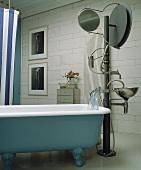 Badewanne im Vintagestil und künstlerische Standarmatur mit Spiegel und Waschbecken an Säule