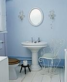Traditionelles blaues Badezimmer mit Standwaschbecken und Stuhl aus weißem Metall