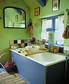 Altes grün gestrichenes Badezimmer unter Dach mit Badewanne am Fenster