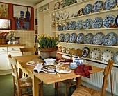 Esstisch mit Frühstück vor Wandregal mit blau weißen Tellern