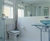 Modernes Badezimmer mit Waschtisch aus Glas und Metall vor grossflächigem Wandspiegel