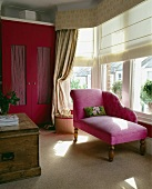 Chaiselongue mit rosa Stoffbezug im Erker mit Raffrollos vor Fenster