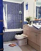 Badewanne vor Wand mit blauen Mosaikfliesen und Waschtisch aus Holz