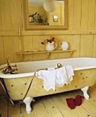 Gelbe freistehende Badewanne im Vintagelook vor gelber Holzwand