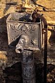 Alte Wasserpumpe vor Natursteinwand