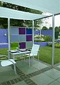 Terrassentisch und Stühle aus Metall unter moderner Pergola mit Gartenblick