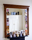 A mirror with an antique wooden frame and a collection of jugs on the shelf below
