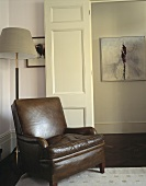 An old brown leather armchair in the corner of a living room next to an open door