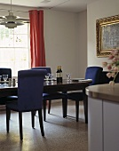 A dark wood dining table and blue upholstered chairs
