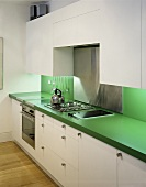 A white kitchen with a green work surface and a splash guard
