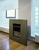 A modern fireplace with a stone frame and a glass stone wall