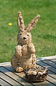 A straw rabbit figure with a nest on wooden boards