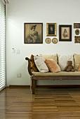Antike Sitzbank und Bildersammlung an Wand im Raum mit Parkettboden