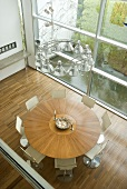 View of a round wooden table and white chairs in front a window bank in a modern living room