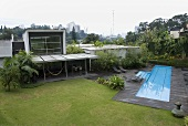 A garden of a newly built house with a pool and a glass facade