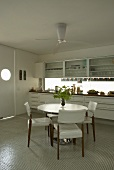 A dining table with upholstered chairs in front of a white kitchen counter in modern kitchen
