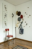 A metal chair with a red seat in the corner of a room next to hat collection on the wall