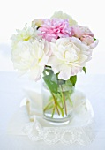Peonies in a vase on a lace cloth